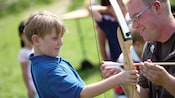 A young male Guest gripping a bow as a Cast Member instructs him during an exciting archery lesson