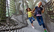 Deux visiteuses rient tandis qu'elles explorent une aire de jeux conçue entièrement de filets au Club Disney