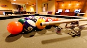 Close-up of racked pool balls, a cue stick, holder and chalk sitting on a pool table
