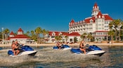 Guests riding 3 personal watercrafts on Seven Seas Lagoon in front of Disney's Grand Floridian Resort & Spa