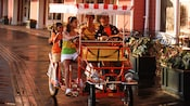 Family of 4 in a fringe-canopied quad-cycle pedal car