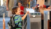 A young boy walks through a turnstile at a Disneyland theme park