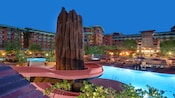 A tall rock formation in front of a lighted pool at Disney's Grand Californian Hotel & Spa
