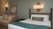 A bedroom containing a large sized bed with a rustic wooden headboard and upholstered love seat