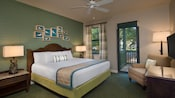 A hotel room with a king sized bed and upholstered arm chair with a door and window opening to a shady yard