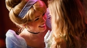 Cinderella smiles during a face-to-face encounter with a young female Guest wearing glasses