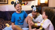 A family of four sits on a bed at Disney's Paradise Pier Hotel and consults a map of Disneyland Resort