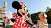 Minnie Mouse holds a young girl's hand in front of Sleeping Beauty Castle at Disneyland park