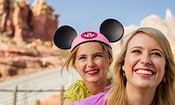 A smiling daughter wearing Mickey ears and her smiling mother stand within Cars Land near the Radiator Springs Racers attraction