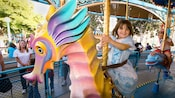 A girl rides a pastel seahorse on King Triton's Carousel