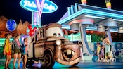 Guests meet Tow Mater in front of Flo's V8 Cafe in Cars Land at Disneyland Resort