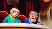 Statler and Waldorf wear 3D glasses while they watch the Muppet Vision 3D show from their balcony
