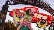 A girl sits on her dad's shoulders beneath the sign for the Radiator Springs Racers FASTPASS Return