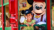 Conductor Mickey and a girl in the front window of a Red Car Trolley