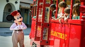 Mickey stops next to a Red Car Trolley to say hello to kids inside