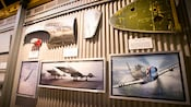 Framed photos and parts of aircraft hanging on a wall in the queue at Soarin' Over California