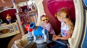 Two girls smile from their Toy Story Maina! vehicle