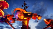 The Astro Orbitor rockets glow warm red as the sun sets at Disneyland Park