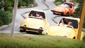A kid drives an Autopia car while her mother helps her steer