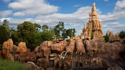 The Big Thunder Mountain Railroad train crests a cliff where dinosaur bones are exposed below