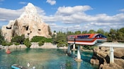 A Disneyland Monorail travels above the Finding Nemo Submarine Voyage attraction and toward Matterhorn Bobsleds