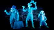 Three hitchhiking ghosts stick their thumbs out to catch a ride through Haunted Mansion