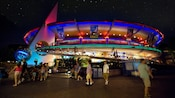 Exterior of the circular Innoventions building lit in neon at night