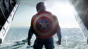 With his shield on his back, Captain America stands ready to jump from a fighter plane