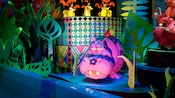 A pink Hippo stands close to water in the Africa scene at the it's a small world attraction