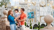 A father and mother hold their son at the entrance to it's a small world