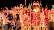 A girl in her father's arms smiles at her mother in front of the sparkling holiday version of it's a small world