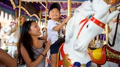 A mother stands next to her smiling son who sits on a King Arthur Carrousel horse