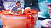 A father and sons enjoy the Mad Tea Party attraction, inspired by Disney's Alice in Wonderland
