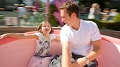 Disneyland Park is a blur as a father spins a Mad Tea Party teacup and his daughter holds on tight