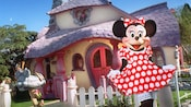 Minnie curtsies to welcome those who come for a Character meet-and-greet at the Minnie's House attraction