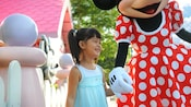 In front of Minnie's House in Disneyland Park, Minnie and a smiling girl hold hands