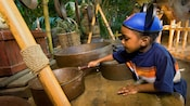 A boy plays with musical cooking pots at Tarzan's Treehouse