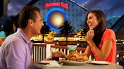 A couple enjoys drinks and food at Cove Bar near California Screamin' in Paradise Pier