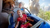 A girl and her parents ride Matterhorn Bobsleds