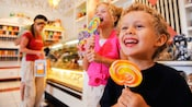 Two little kids enjoy large lollipops at Marceline's Confectionery, a Downtown Disney candy shop