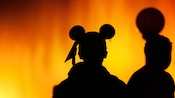 Silhouette of a boy wearing Pirate Mickey Ears against the Pirate chapter of World of Color