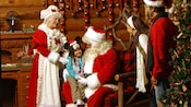Mrs. Claus smiles happily, as a little girl sits on Santa's lap