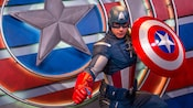 Captain America holds his shield and strikes a heroic pose directly in front of his patriotic symbol