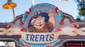 A colorful wooden sign at Fantasy Faire reads, 'Maurice's Treats'