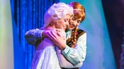 Queen Elsa and her sister Anna smiling while enjoying a warm hug at Fantasy Faire in Disneyland Park