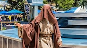 A Jedi Knight with a cowl over his face gestures with his right hand