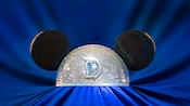 Encrusted with sapphires and other jewels, glittering Mickey Ears sit atop a velvet display