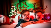 Two boys smiling on their hotel room bed each wearing antlers and a red nose