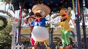 Donald Duck entertains on stage with Panchito the rooster and José Carioca the parrot