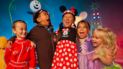A group of kids in costumes laugh during Mickey's Halloween Party at Disneyland Park